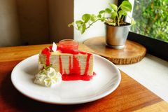 Acrespone la torta con crema y la fresa en el top y la salsa en de cerámica imagen de archivo