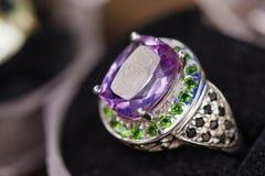 Acro射击了在礼物盒的银色定婚戒指在五颜六色,闪耀的背景 免版税图库摄影