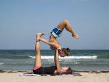 Acro scorpion pose. Beautiful girls performing an advanced acro yoga balance at the sea coast of Sozopol,Bulgaria Royalty Free Stock Image