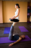 Acro yoga. Girl sitting in padmasana, lotus pose on feet of man indoors Stock Photo