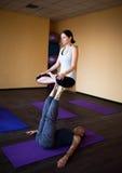 Acro-Yoga Mädchen, das zuhause im padmasana, Lotoshaltung auf Füßen des Mannes sitzt Lizenzfreies Stockbild