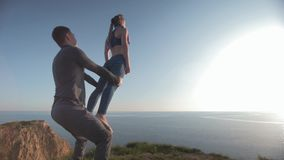 Acro yoga, sports girl with hands raised is balancing on legs of male partner on background of blue sky and river with. Acro yoga, sports girl with hands raised stock video