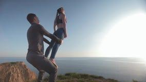 Acro-Yoga, trägt Mädchen mit den angehobenen Händen balanciert auf Beinen des männlichen Partners auf Hintergrund des blauen Himm stock video