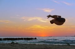 Acrobacia no mar, acrobata no por do sol da costa de mar, salto mortal na praia imagem de stock royalty free