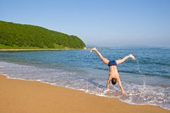 Acrobat. The young man somersaults on seacoast. Splashes and sand on a background of the sky Royalty Free Stock Images