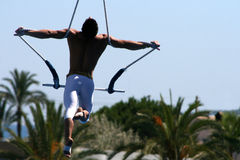 Acrobat #2. Man doing acrobatic figures above palm trees Royalty Free Stock Images