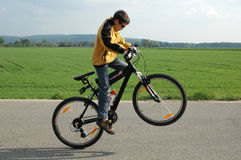Acrobat on bicycle. Young boy do actrobatics on his bicycle outside Royalty Free Stock Image