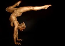 Acrobat dancer toned in gold  posing over black background Royalty Free Stock Photo