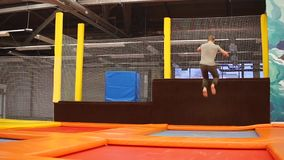 Sportsman is performing acrobatic elements on a trampoline stock video footage