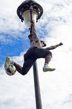 Acrobat performs a stunt with a ball on top of a lamppost. Royalty Free Stock Images
