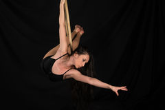 Acrobat. Petite young brunette on an aerial ring Royalty Free Stock Photo