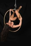 Acrobat. Petite young brunette on an aerial ring Stock Image