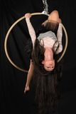 Acrobat. Petite young brunette on an aerial ring Royalty Free Stock Photos