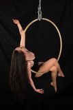 Acrobat. Petite young brunette on an aerial ring Royalty Free Stock Images