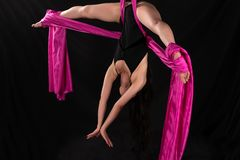 Acrobat. Petite young brunette suspended from a purple fabric Stock Photo