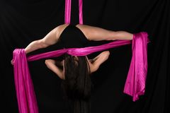 Acrobat. Petite young brunette suspended from a purple fabric Royalty Free Stock Photography