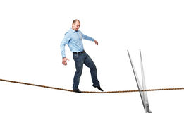 Acrobat on rope. Young businessman try to walk on rope and silver scissor Stock Photo