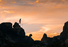 An acrobat walking the slackline. Between two mountains at dusk with an orange sky in the background Royalty Free Stock Photography
