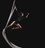 Acrobat woman in gymnast suit. Posing isolated on a black background Stock Photo