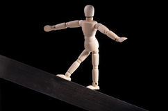 Acrobat. A wooden mannequin walking on a metal board as an acrobat on a black background Royalty Free Stock Photo