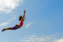 Acrobata femminile di volo davanti a cielo blu Fotografie Stock