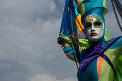 Acrobate dans le masque coloré dans le ciel bleu photographie stock libre de droits