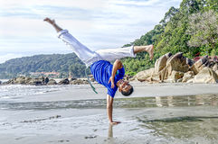 Acrobatic action of capoeira instructor on the beach Stock Photo