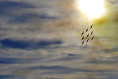 Acrobatic aircraft. In a perfect figure during an airshow at sunset Stock Photos