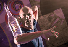 Acrobatic Barman in Action - Freestyle american Bartender. Frontal amazong view of an acrobatic barman performing freestyle moves with a bottle on the elbow Royalty Free Stock Image