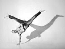 Acrobatic Breakdance Kick. Young man in the 20s performing an acrobatic breakdance kick. Shot in a studio on a white background Stock Image