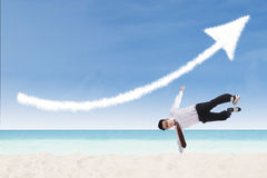 Acrobatic businessman perform success move at beach. Happy businessman perform success move at beach under up arrow sign Stock Photography
