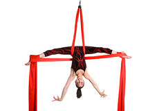 Acrobatic girl exercising on red fabric rope Stock Images