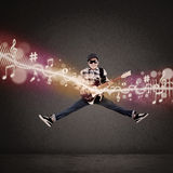 Acrobatic guitarist jumping with musical notes Royalty Free Stock Image