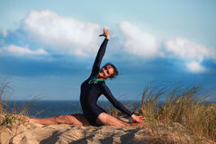 Acrobatic gymnast is doing the split on the beach Stock Photo
