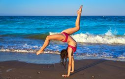 Acrobatic gymnastics bikini girl in a beach. Blue shore at summer stock images