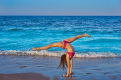 Acrobatic gymnastics bikini girl in a beach stock image