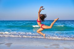Acrobatic gymnastics bikini girl in a beach. Blue shore at summer royalty free stock photography