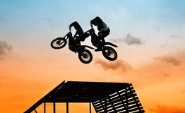 Acrobatic jump. With motorbike at sunset Royalty Free Stock Photos