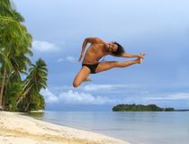 Acrobatic jump on tropical beach. Asian boy performing an acrobatic dance or ballet  jump pose on a pristine tropical beach with palm trees on the edge and a Stock Images
