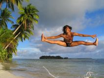 Acrobatic jump on tropical beach. Asian boy performing an acrobatic dance or ballet  jump on a pristine tropical beach with palm trees and a pristine island in Royalty Free Stock Photos