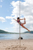 Acrobatic performance brunette in swimsuit on pole for dancing Stock Photography