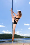 Acrobatic performance girl in bathing suit on pole for dancing Royalty Free Stock Photo