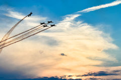 Acrobatic planes in action at an Airshow flying at sunset / dusk Stock Photos
