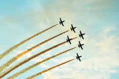 Acrobatic planes doing acrobatics at an Airshow flying at sunset Stock Photography
