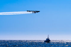Acrobatic planes fly over a ship in the sea Stock Photos
