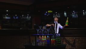 Acrobatic show performed by barman juggling bottle. bar background Stock Image
