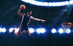 Acrobatic slam dunk of a basket player in the basket at the stadium. Basketball player slams dunk the ball to the basket royalty free stock photos