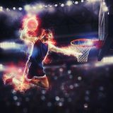 Acrobatic slam dunk of a basket player in the basket at the stadium. Basketball player slams dunk the ball to the basket royalty free stock photo