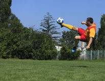 Acrobatic soccer player. A soccer player kicking the ball in an acrobatic position Stock Images