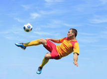 Acrobatic soccer player. A soccer player kicking the ball in an acrobatic position Stock Photography